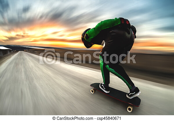 A man in a helmet and leather suit, in a rack at high speed, rides on a long longboard for downhill on afsalt against the backdrop of the setting sun in the light of the setting sun. - csp45840671
