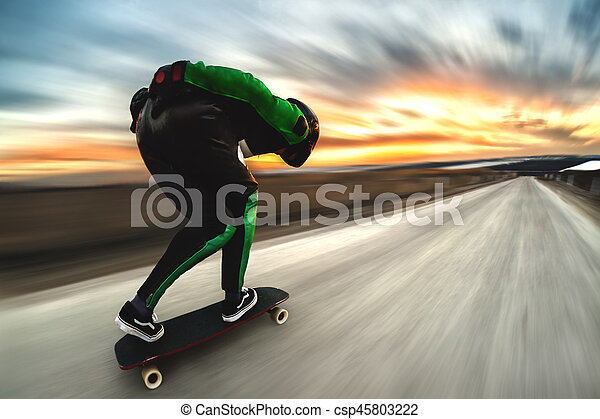 A man in a helmet and leather suit, in a rack at high speed, rides on a long longboard for downhill on afsalt against the backdrop of the setting sun in the light of the setting sun. - csp45803222