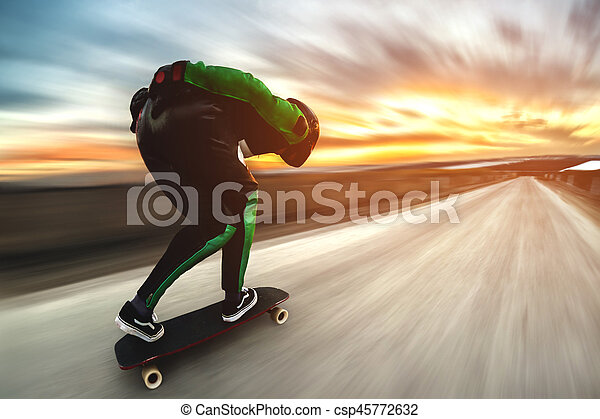 A man in a helmet and leather suit, in a rack at high speed, rides on a long longboard for downhill on afsalt against the backdrop of the setting sun in the light of the setting sun. - csp45772632