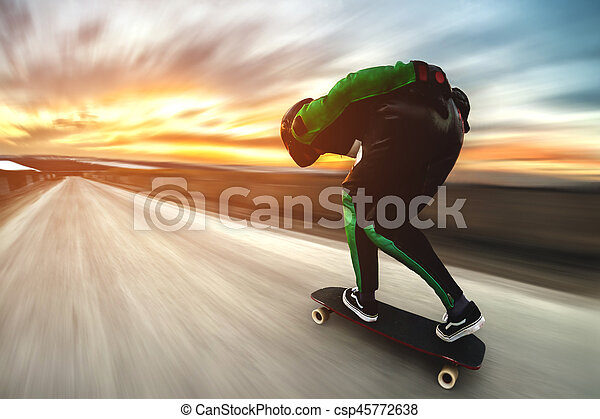 A man in a helmet and leather suit, in a rack at high speed, rides on a long longboard for downhill on afsalt against the backdrop of the setting sun in the light of the setting sun. - csp45772638