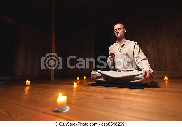 a man in gray linen clothes sits in lotus position in a