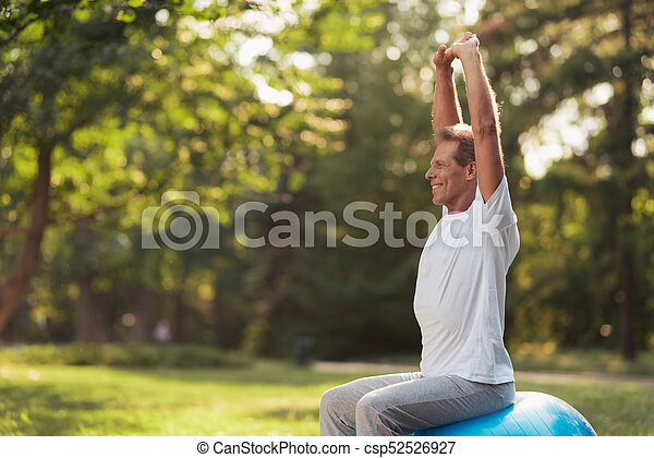 A man is engaged in a yoga park with a blue yoga ball. He is sitting on the ball raising his hands up - csp52526927
