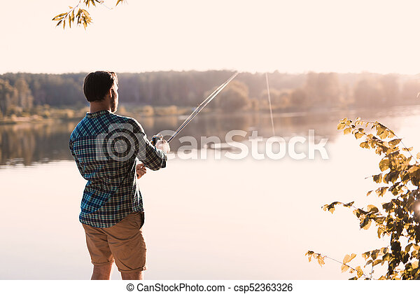 A man is fishing on the river bank. He stands with his back to the camera against the background of the river - csp52363326