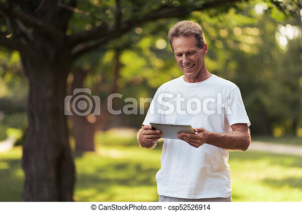 A man is standing in a park with a gray tablet in his hands. He looks at the tablet screen - csp52526914