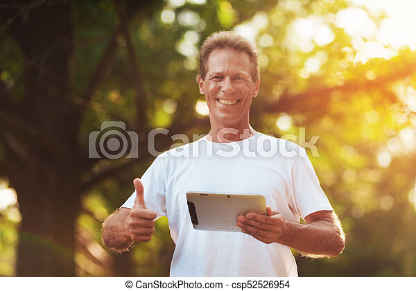 A man is standing in a park with a gray tablet in his hands. He looks at the camera and shows a thumbs up. - csp52526954