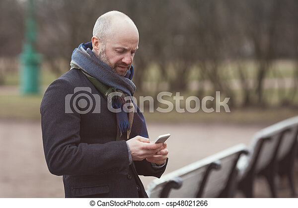 A man is standing in the street and waiting for someone. He looks at his phone and dials a number. - csp48021266