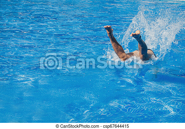 a man jumps into the pool. Swimmer in the water - csp67644415