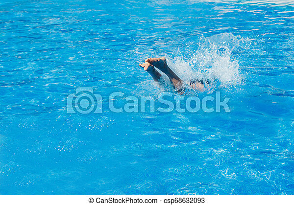 a man jumps into the pool. Swimmer in the water - csp68632093
