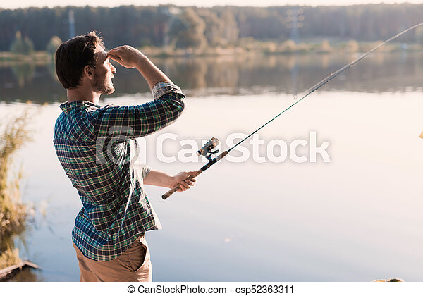 A man looks out on the river, holding a spinning rod in front of the river - csp52363311