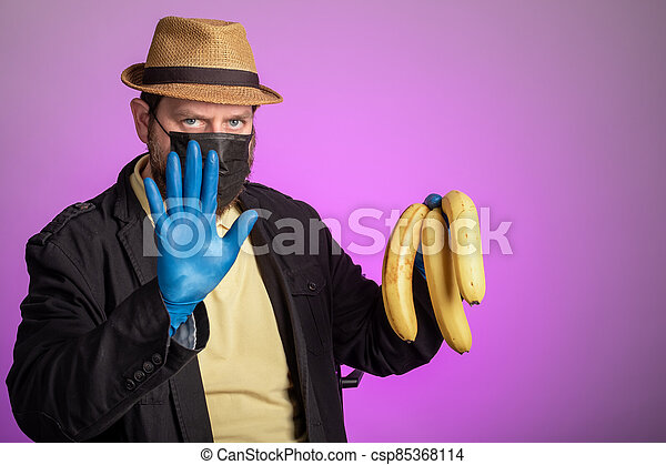 a man makes a gesture with his hand calls to stop, in the other hand bananas - csp85368114
