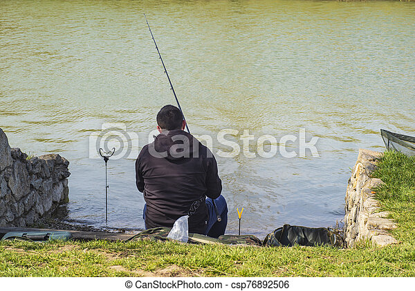 A man on the riverbank with a fishing rod catches a fish. Spring warm day man with fishing rod , man standing on the riverbank fishing fish. - csp76892506