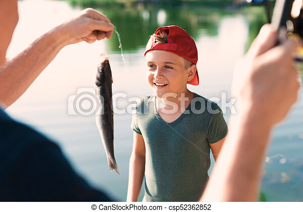 A man shows the boy in a red cap a fish he just caught on his spinning - csp52362852