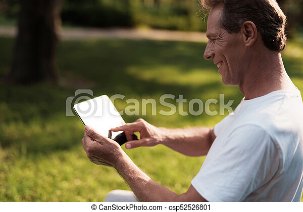 A man sits on a ball for yoga and looks at something on his tablet. He smiles - csp52526801