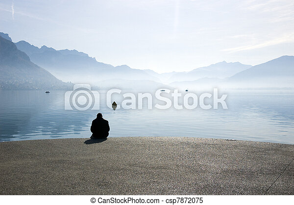 A man sitting at edge of the lake of annecy, in front of mountains on morning. France - csp7872075