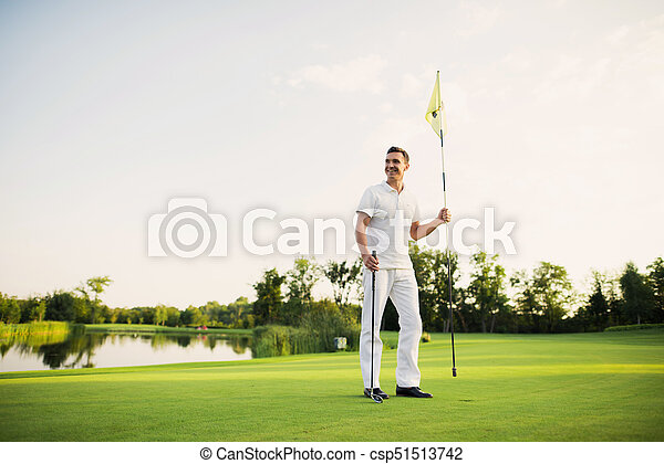 A man stands on a golf course, holds a golf club and flags for the hole - csp51513742