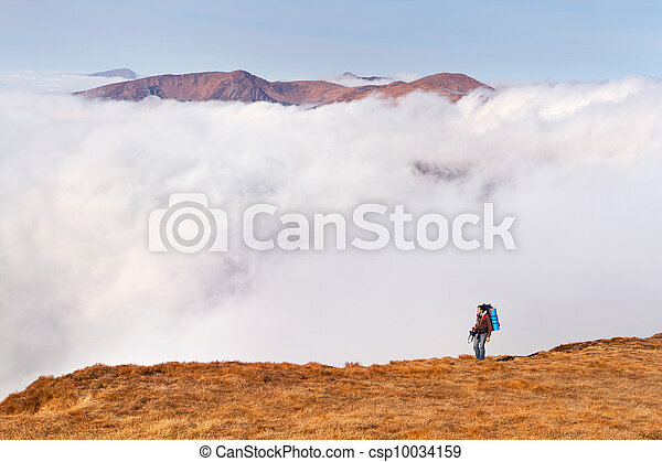 A man with a backpack is on the edge of cliffs in the mountains - csp10034159