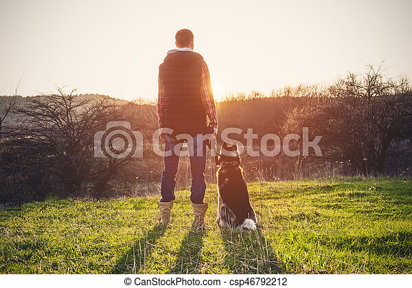 A man with a beard walking his dog in the nature, standing with a backlight at the rising sun, casting a warm glow and long shadows against the background of the gorge and trees. - csp46792212