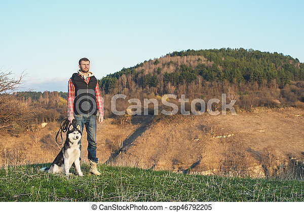 A man with a beard walking his dog in the nature, standing with a backlight at the rising sun, casting a warm glow and long shadows against the background of the gorge and trees. - csp46792205