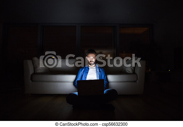 A man working on a laptop at home at night. - csp56632300