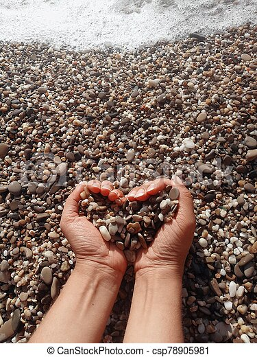 A man's hand holds a handful of stones - csp78905981