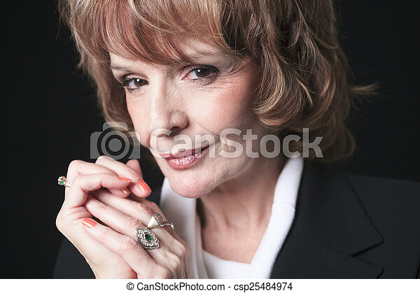 A Mature Business woman isolated on black background - csp25484974