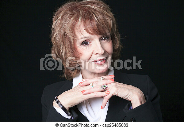 A Mature Business woman isolated on black background - csp25485083