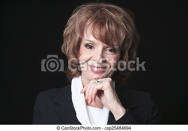 A Mature Business woman isolated on black background - csp25484694