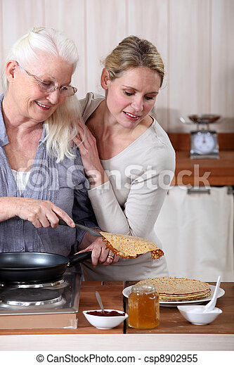 A mature mother and her adult daughter making crepes. - csp8902955