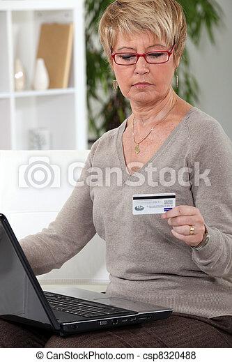A mature woman doing online shopping. - csp8320488