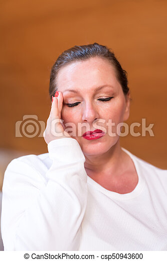 A middle aged woman suffering from migraine - csp50943600