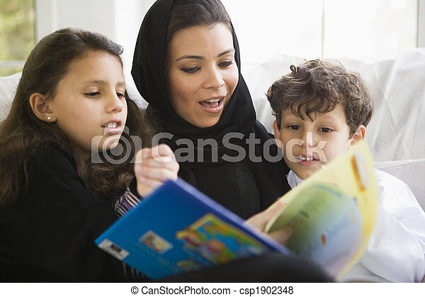 A Middle Eastern family reading a book together - csp1902348