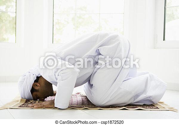 A Middle Eastern man praying - csp1872520