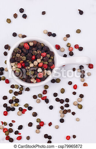 A mixture of multi-colored pepper in a small dish - csp79965872