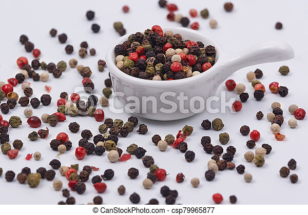 A mixture of multi-colored pepper in a small dish - csp79965877