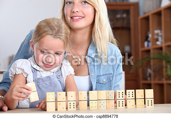 A mother and daughter playing with dominos. - csp8894778