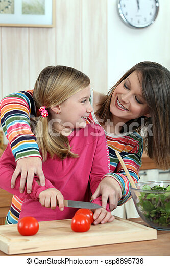 A mother teaching her daughter how to cook. - csp8895736