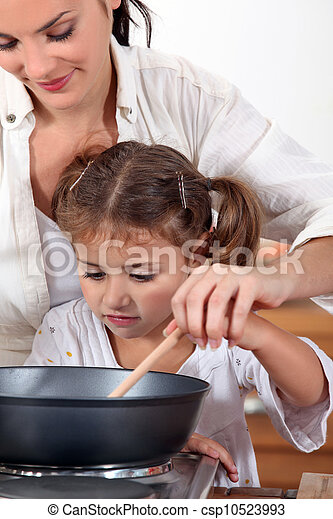 A mother teaching her daughter how to cook. - csp10523993