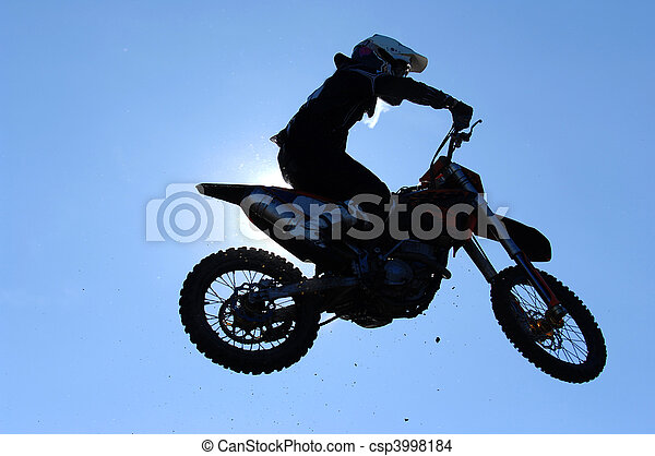 A motorcross rider in the air during a race. - csp3998184