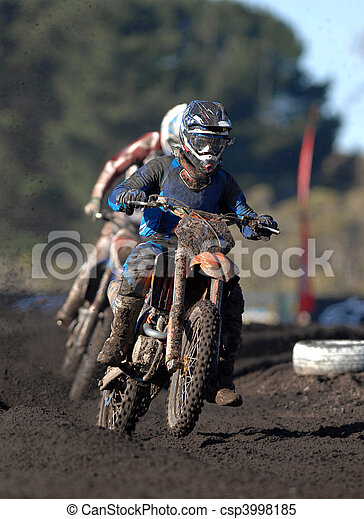 A muddy motocross rider in action during a race - csp3998185