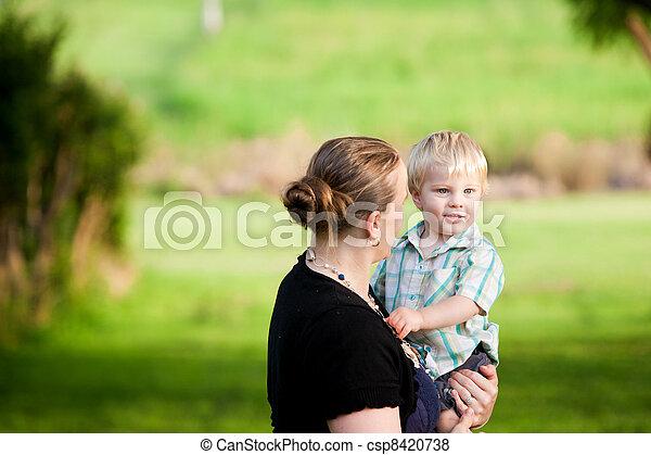 A mum cuddles her little boy in an outdoor green field.   - csp8420738