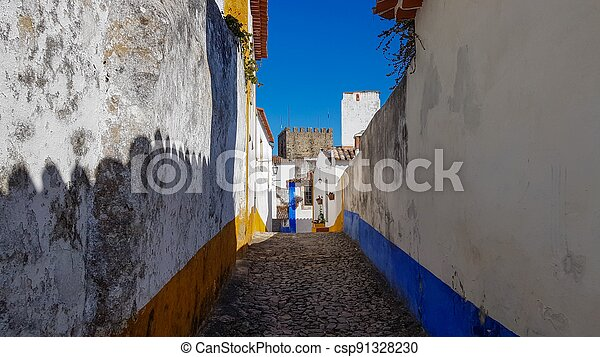 a narrow street inside of the obidos castle in Portugal - csp91328230