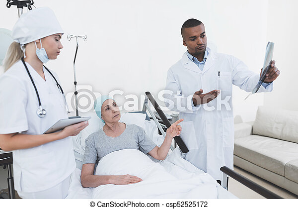 A nurse is stand against the patient's background. She holds a tablet in her hands. - csp52525172