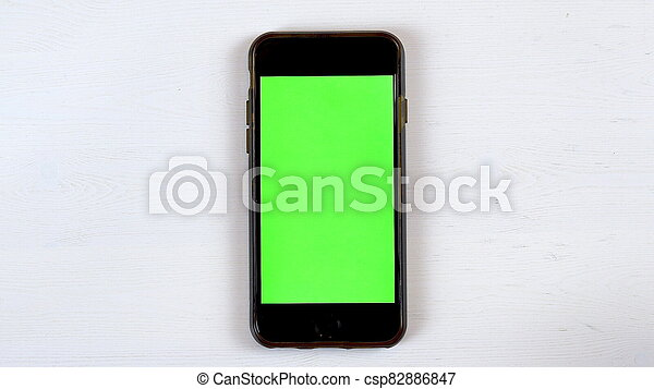 A phone with a green screen lies on the table. Chroma Key on Gadget Screen. - csp82886847