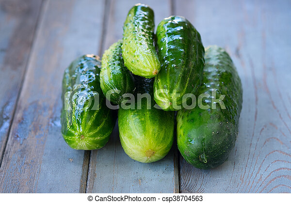 A pile of fresh picked cucumbers on wooden background - csp38704563
