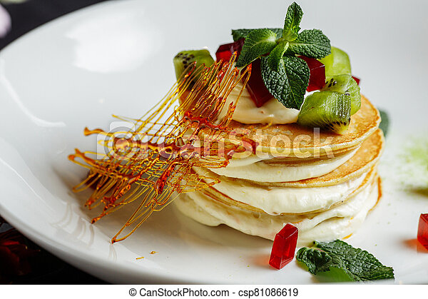 a pile of fritters with cream on a gray blue plate - csp81086619