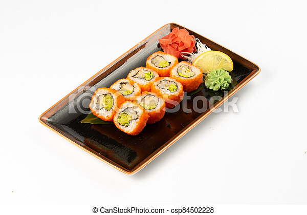 A portion of maki sushi with an assortment of Japanese side dishes in a rectangular ceramic plate on a white plate. - csp84502228