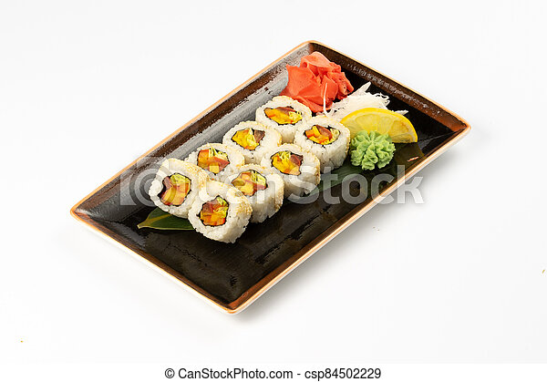 A portion of maki sushi with an assortment of Japanese side dishes in a rectangular ceramic plate on a white plate. - csp84502229