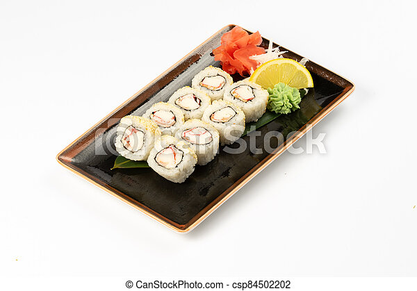 A portion of maki sushi with an assortment of Japanese side dishes in a rectangular ceramic plate on a white plate. - csp84502202