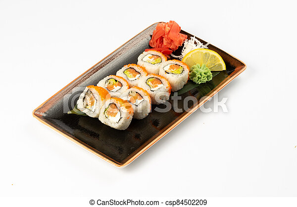 A portion of maki sushi with an assortment of Japanese side dishes in a rectangular ceramic plate on a white plate. - csp84502209