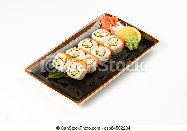 A portion of maki sushi with an assortment of Japanese side dishes in a rectangular ceramic plate on a white plate. - csp84502234